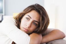 Das Foto zeigt eine nachdenkliche Frau. Die Diagnose Endometriose kann vor allem für Frauen belastend sein.