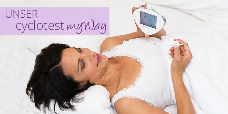 Frau liegt im Bett mit eingeschaltetem Zykluscomputer cyclotest myWay.