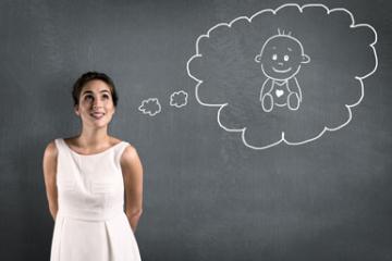 Eine Frau mit Kinderwunsch stellt sich in einer Gedankenblase ihr Wunschbaby vor.