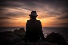Nachdenkliche Frau sitzt auf Felsen am Meer und sieht dem Sonnenuntergang zu.