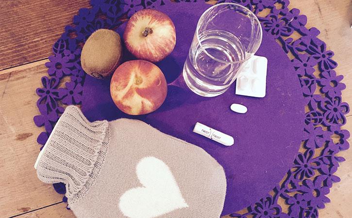 Regelschmerzen können durch Medikamente und Hausmittel wie Wärmflasche und gesunde Ernährung gelindert werden.